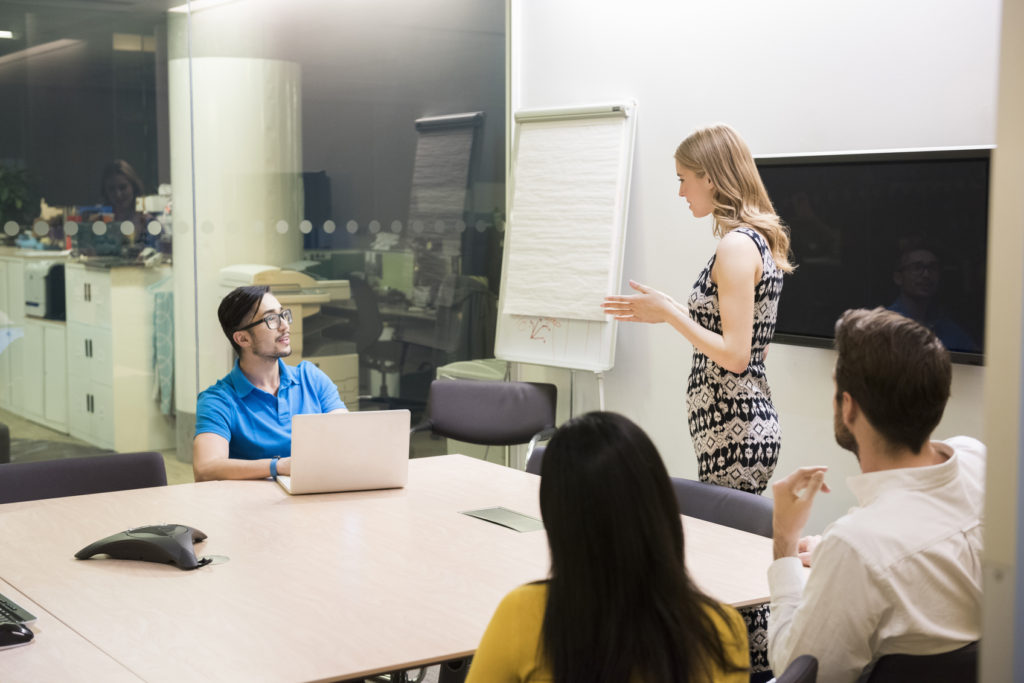 A photo of businesswoman giving presentation to colleagues at conference table. Business people are in board room. Concentrated associates listening to presentation, in a brightly lit modern office.