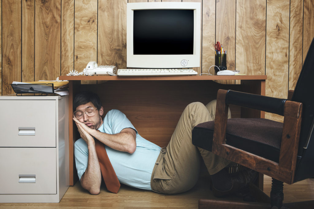 A man and office in 1980's - 1990's style, complete with vintage computer and technology of the time, sleeps under his desk, too tired and bored to continue working. Wood paneling on the wall in the background.